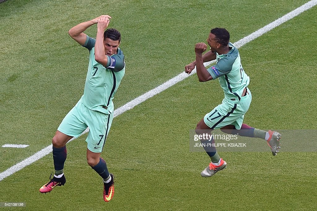 TOPSHOT - Portugal's forward Cristiano Ronaldo (L) celebrates after scoring a goal during the Euro 2016 group F football match between Hungary and Portugal at the Parc Olympique Lyonnais stadium in Decines-Charpieu, near Lyon, on June 22, 2016. / AFP / JEAN