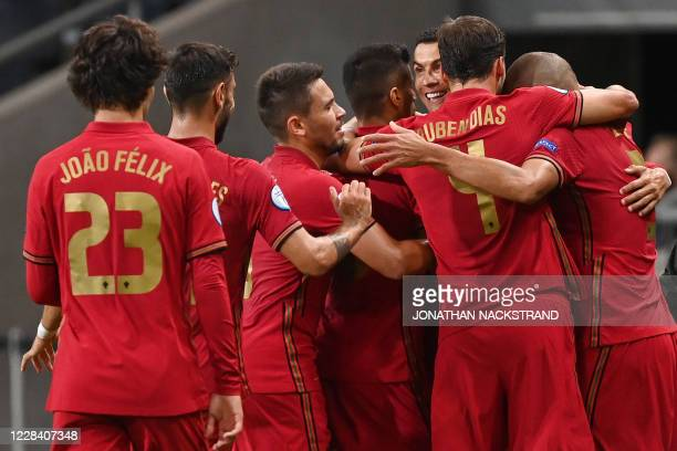 Portugal's forward Cristiano Ronaldo celebrates scoring the opening goal, his 100th goal for Portugal, with his team-mates during the UEFA Nations...