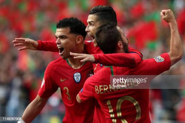 Portugal's forward Cristiano Ronaldo celebrates with forward Bernardo Silva and defender Pepe after scoring a goal during the UEFA Nations League...