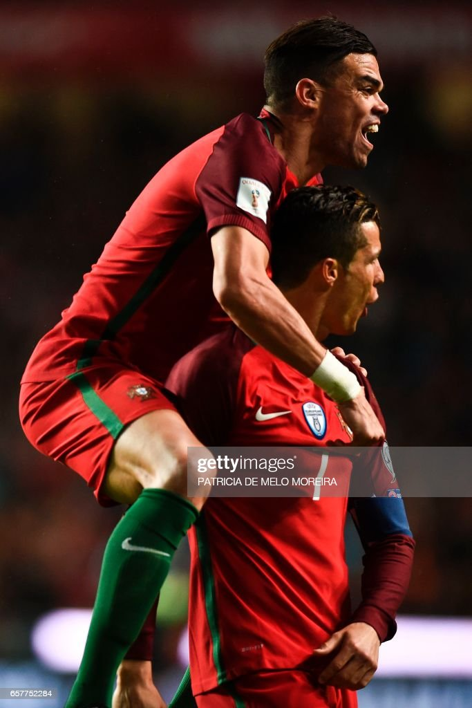Portugal's forward Cristiano Ronaldo (R) celebrates with his teammate Portugal's defender Pepe (L) after scoring during the WC 2018 group B football qualifing match Portugal vs Hungary at the Luz stadium in Lisbon on March 25, 2017. /