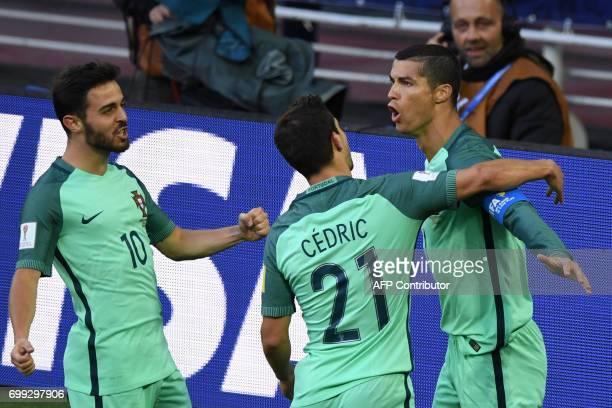 Portugal's forward Cristiano Ronaldo celebrates with Portugal's defender Cedric and Portugal's midfielder Bernardo Silva after scoring a goal during...