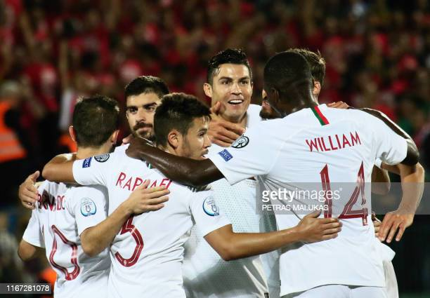 TOPSHOT Portugal's forward Cristiano Ronaldo celebrates with teammates after scoring during the UEFA Euro 2020 Group B qualification football match...