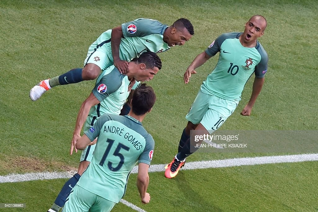 Portugal's forward Cristiano Ronaldo (C) celebrates with teammates after scoring a goal during the Euro 2016 group F football match between Hungary and Portugal at the Parc Olympique Lyonnais stadium in Decines-Charpieu, near Lyon, on June 22, 2016. / AFP / JEAN