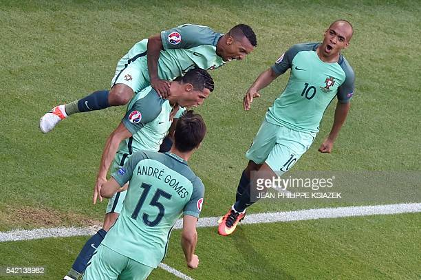Portugal's forward Cristiano Ronaldo celebrates with teammates after scoring a goal during the Euro 2016 group F football match between Hungary and...