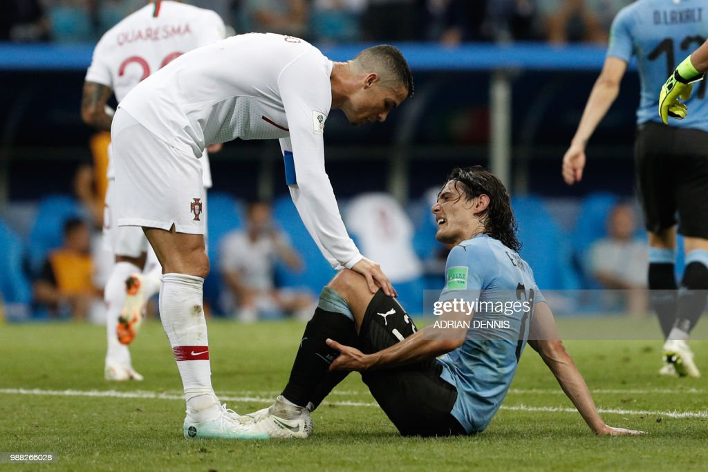 Portugal's forward Cristiano Ronaldo (L) checks on Uruguay's forward Edinson Cavani during the Russia 2018 World Cup round of 16 football match between Uruguay and Portugal at the Fisht Stadium in Sochi on June 30, 2018. (Photo by Adrian DENNIS / AFP) / RESTRICTED