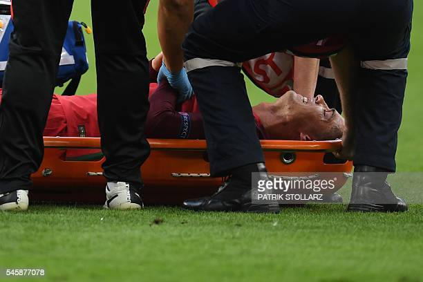 Portugal's forward Cristiano Ronaldo cries as he lies in a stretcher after being injured during the Euro 2016 final football match between Portugal...