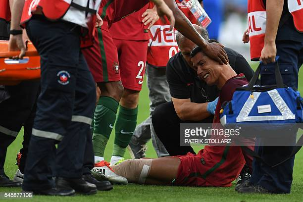 Portugal's forward Cristiano Ronaldo cries as he receives medical attention after being injured during the Euro 2016 final football match between...