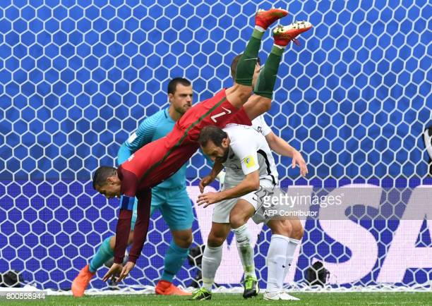 Portugal's forward Cristiano Ronaldo falls over New Zealand's defender Andrew Durante after missing a goal during the 2017 Confederations Cup group A...
