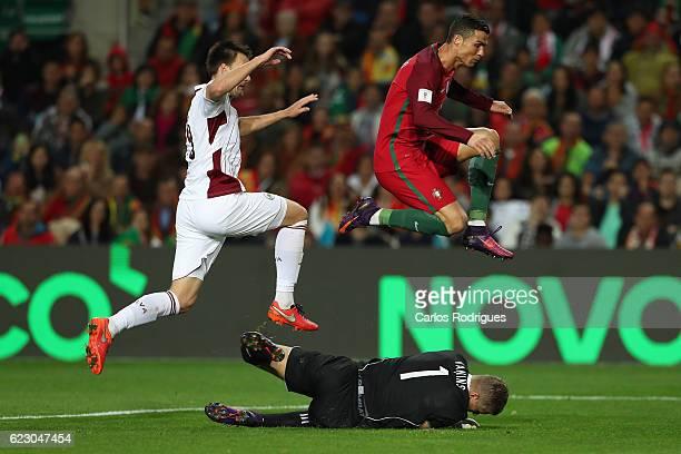 Portugal's forward Cristiano Ronaldo from Portugal jumps to avoid hit Latvia's goalkeeper Andris Vanina from Latvia during the Portugal v Latvia FIFA...