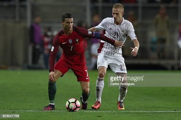 Portugal's forward Cristiano Ronaldo from Portugal vies with Latvia's midfielder Gleb Kluskina from Latvia during the Portugal v Latvia FIFA 2018...