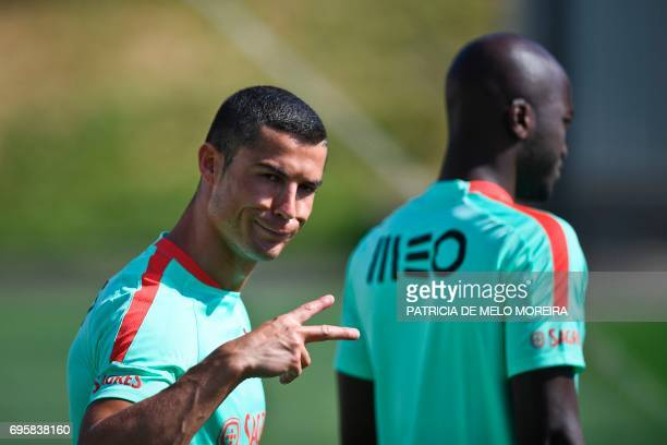 Portugal's forward Cristiano Ronaldo gestures as he arrives for a training session at Cidade do Futebol training camp in Oeiras outskirts of Lisbon...