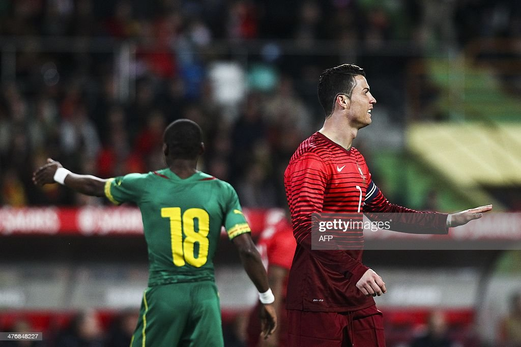 Portugal's forward Cristiano Ronaldo (R) gestures next to Cameroon's midfielder Eyong Enoh (L) during the FIFA 2014 World Cup friendly football match Portugal vs Cameroon at Magalhaes Pessoa stadium in Leiria on March 5, 2014.