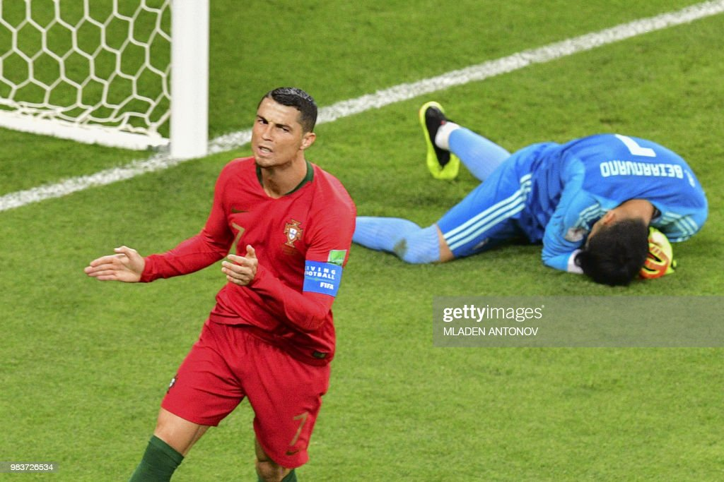 TOPSHOT - Portugal's forward Cristiano Ronaldo has a shot saved by Iran's goalkeeper Alireza Beiranvand (R) during the Russia 2018 World Cup Group B football match between Iran and Portugal at the Mordovia Arena in Saransk on June 25, 2018. (Photo by Mladen ANTONOV / AFP) / RESTRICTED