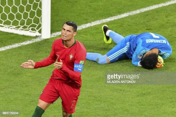 TOPSHOT Portugal's forward Cristiano Ronaldo has a shot saved by Iran's goalkeeper Alireza Beiranvand during the Russia 2018 World Cup Group B...