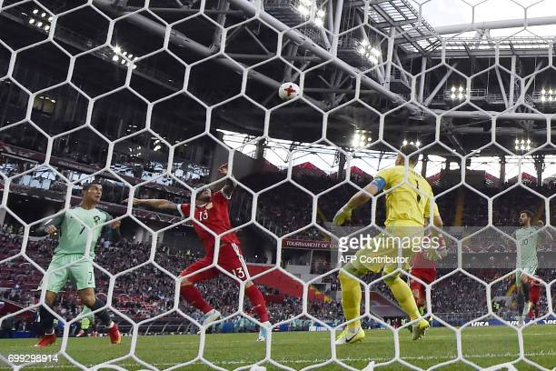 Portugal's forward Cristiano Ronaldo heads the ball to score past Russia's goalkeeper Igor Akinfeev during the 2017 Confederations Cup group A...
