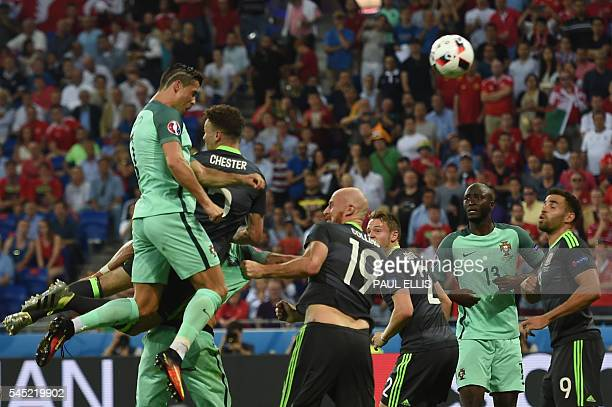 Portugal's forward Cristiano Ronaldo heads the ball to score the opening goal during the Euro 2016 semifinal football match between Portugal and...
