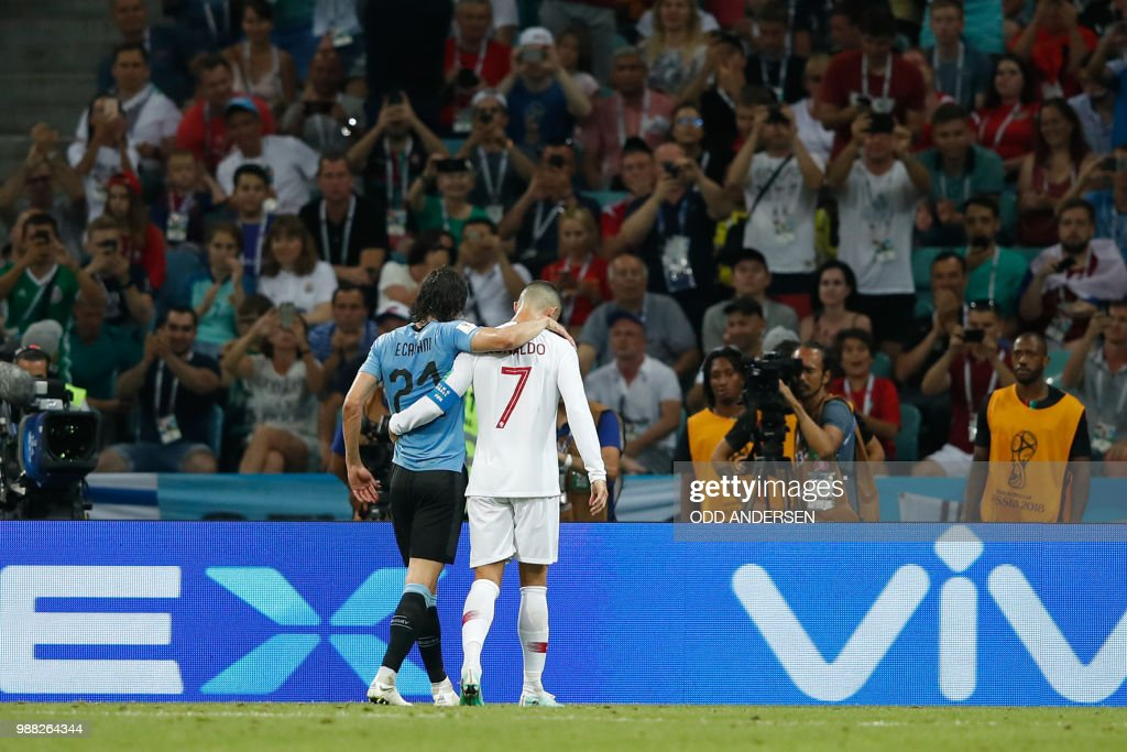 TOPSHOT - Portugal's forward Cristiano Ronaldo (R) helps Uruguay's forward Edinson Cavani after he picked up an injury during the Russia 2018 World Cup round of 16 football match between Uruguay and Portugal at the Fisht Stadium in Sochi on June 30, 2018. (Photo by Odd ANDERSEN / AFP) / RESTRICTED