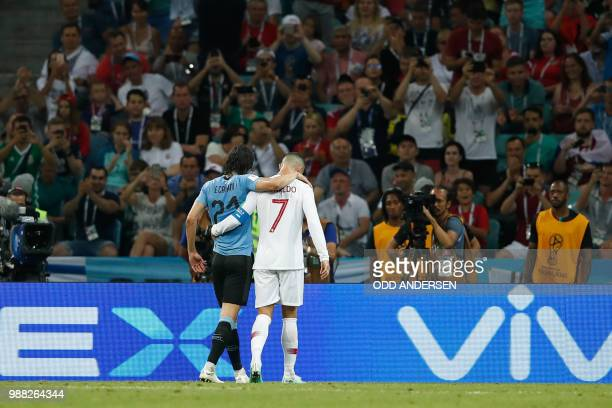 TOPSHOT Portugal's forward Cristiano Ronaldo helps Uruguay's forward Edinson Cavani after he picked up an injury during the Russia 2018 World Cup...