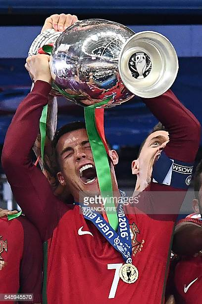 Portugal's forward Cristiano Ronaldo hold up the winners' trophy as he celebrates with teammates after beating France 10 to clinch the Euro 2016...