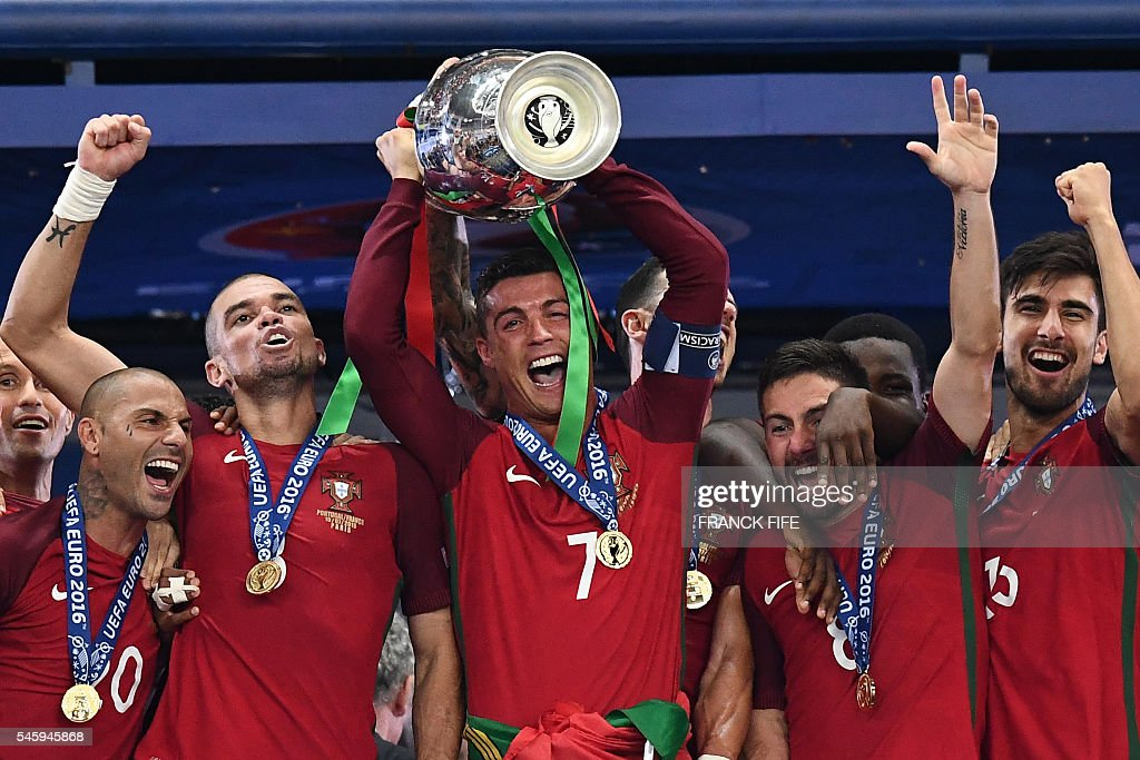 TOPSHOT - Portugal's forward Cristiano Ronaldo hold up the winners' trophy as he celebrates with teammates Portugal's forward Ricardo Quaresma (L), Portugal's defender Pepe, Portugal's midfielder Joao Moutinho and Portugal's midfielder Adrien Silva after beating France 1-0 to clinch the Euro 2016 final football match between France and Portugal at the Stade de France in Saint-Denis, north of Paris, on July 10, 2016. / AFP / FRANCK