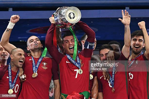 TOPSHOT Portugal's forward Cristiano Ronaldo hold up the winners' trophy as he celebrates with teammates Portugal's forward Ricardo Quaresma...