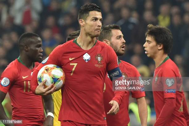 TOPSHOT Portugal's forward Cristiano Ronaldo holds the ball during the Euro 2020 football qualification match between Ukraine and Portugal at the NSK...
