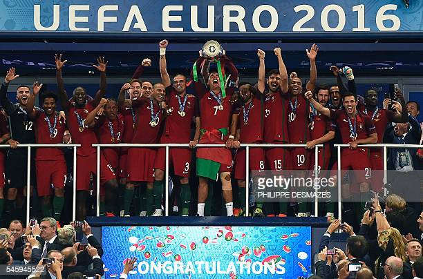 Portugal's forward Cristiano Ronaldo holds up the trophy as he celebrates with teammates after Portugal beat France during the Euro 2016 final...