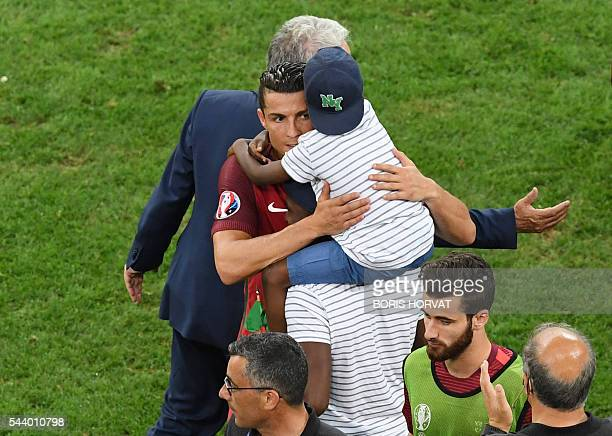 Portugal's forward Cristiano Ronaldo hugs a child after the Euro 2016 quarterfinal football match between Poland and Portugal at the Stade Velodrome...