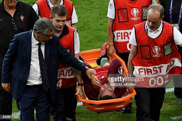 TOPSHOT Portugal's forward Cristiano Ronaldo is comforted by Portugal's coach Fernando Santos as he is carried on a stretcher off the pitch by medics...