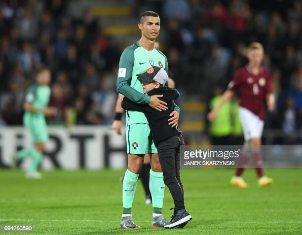 Portugal's forward Cristiano Ronaldo is hugged by a child after the FIFA World Cup 2018 qualification football match between Latvia and Portugal in...