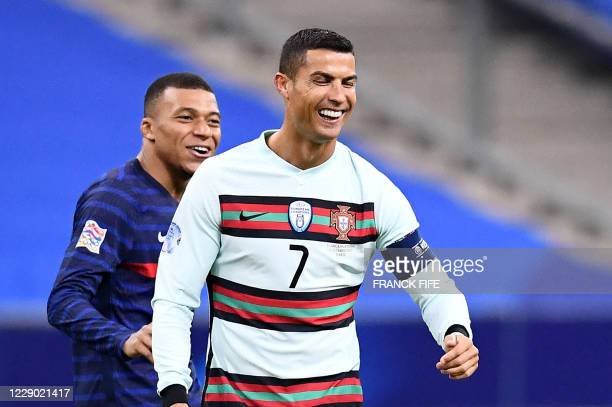 Portugal's forward Cristiano Ronaldo jokes with France's forward Kylian Mbappe during the Nations League football match between France and Portugal,...