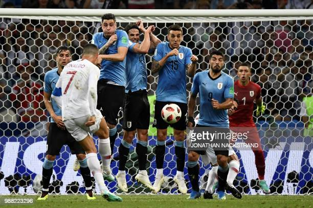 TOPSHOT Portugal's forward Cristiano Ronaldo kicks a free kick during the Russia 2018 World Cup round of 16 football match between Uruguay and...
