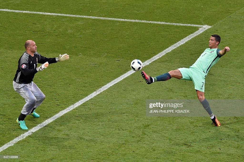 TOPSHOT - Portugal's forward Cristiano Ronaldo (R) kicks the ball in front of Hungary's goalkeeper Gabor Kiraly during the Euro 2016 group F football match between Hungary and Portugal at the Parc Olympique Lyonnais stadium in Decines-Charpieu, near Lyon, on June 22, 2016. / AFP / JEAN