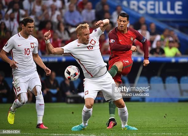 TOPSHOT Portugal's forward Cristiano Ronaldo kicks the ball past Poland's defender Kamil Glik and Poland's midfielder Grzegorz Krychowiak during the...