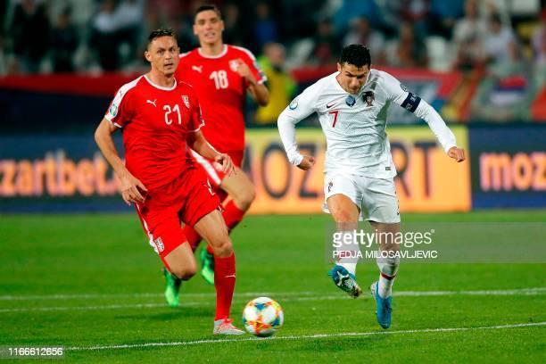 Portugal's forward Cristiano Ronaldo kicks the ball past Serbia's defender Nemanja Matic during the EURO 2020 football qualification match between...