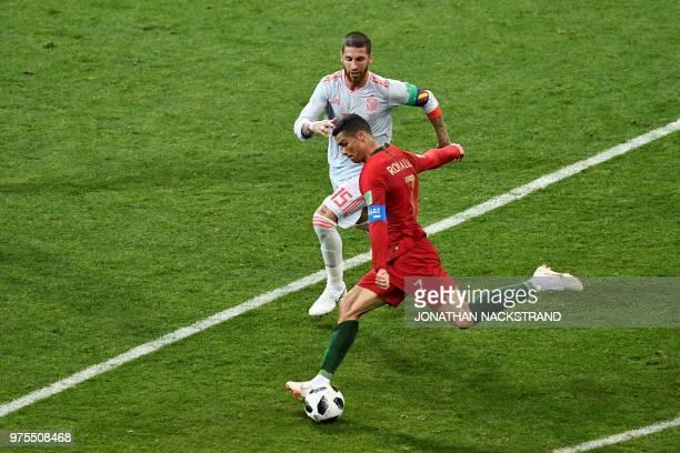 Portugal's forward Cristiano Ronaldo kicks the ball to score despite Spain's defender Sergio Ramos during the Russia 2018 World Cup Group B football...