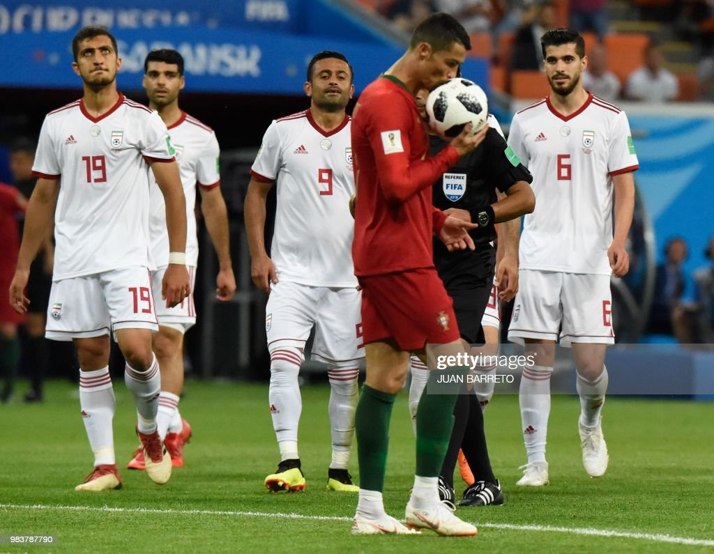 TOPSHOT - Portugal's forward Cristiano Ronaldo (2nd-R) kisses the ball before taking a penalty during the Russia 2018 World Cup Group B football match between Iran and Portugal at the Mordovia Arena in Saransk on June 25, 2018. (Photo by JUAN BARRETO / AFP) / RESTRICTED