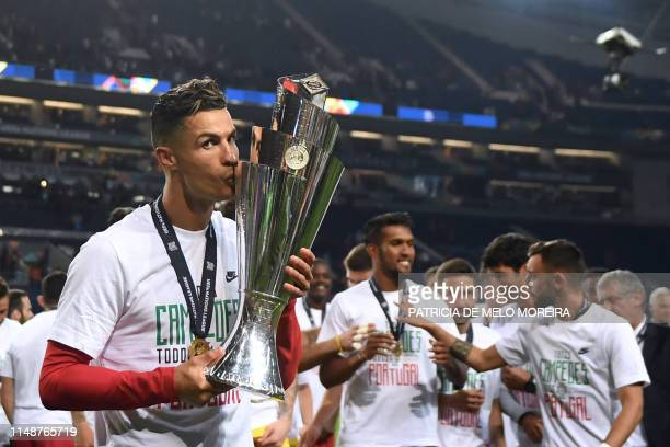 TOPSHOT Portugal's forward Cristiano Ronaldo kisses the trophy after winning the UEFA Nations League final football match between Portugal and The...
