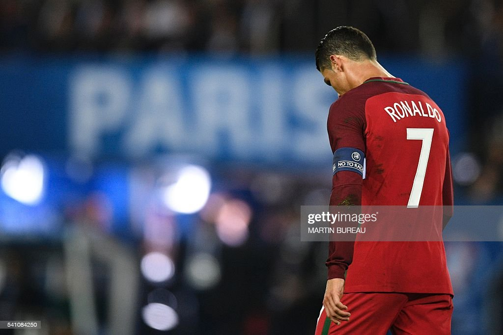 TOPSHOT - Portugal's forward Cristiano Ronaldo reacts after he missed to score a penalty during the Euro 2016 group F football match between Portugal and Austria at the Parc des Princes in Paris on June 18, 2016. / AFP / MARTIN