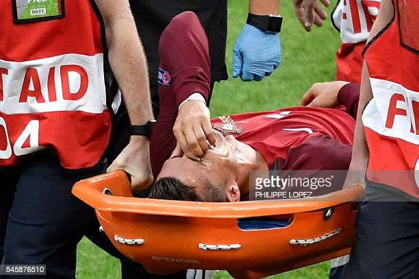 TOPSHOT Portugal's forward Cristiano Ronaldo reacts as he is carried on a stretcher off the pitch by team medics after an injury following a clash...
