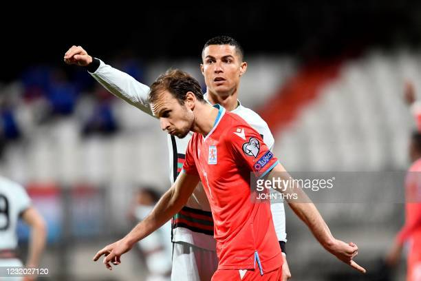 Portugal's forward Cristiano Ronaldo reacts as Luxembourg's midfielder Lars Gerson walks past him during the FIFA World Cup Qatar 2022 qualification...