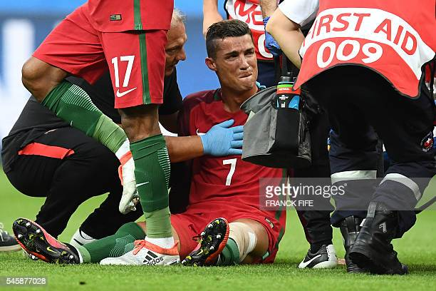 TOPSHOT Portugal's forward Cristiano Ronaldo reacts as medics arrive on the pitch during the Euro 2016 final football match between France and...
