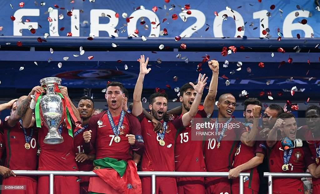 Portugal's forward Cristiano Ronaldo (7) reacts as Portugal's defender Pepe holds up the winners' trophy as the team celebrates beating France 1-0 to clinch the Euro 2016 final football match between France and Portugal at the Stade de France in Saint-Denis, north of Paris, on July 10, 2016. / AFP / FRANCK