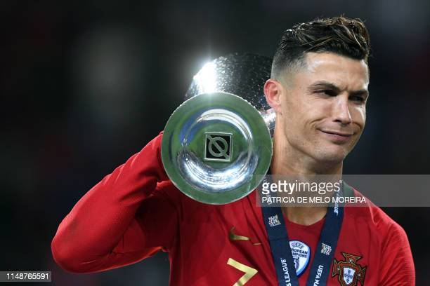 Portugal's forward Cristiano Ronaldo receives the trophy after winning the UEFA Nations League final football match between Portugal and The...