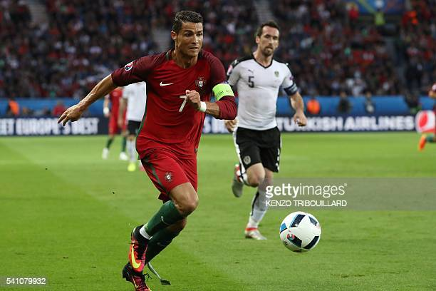 Portugal's forward Cristiano Ronaldo runs with the ball beside Austria's defender Christian Fuchs during the Euro 2016 group F football match between...