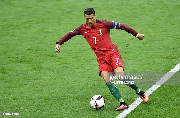 TOPSHOT Portugal's forward Cristiano Ronaldo runs with the ball during the Euro 2016 final football match between Portugal and France at the Stade de...