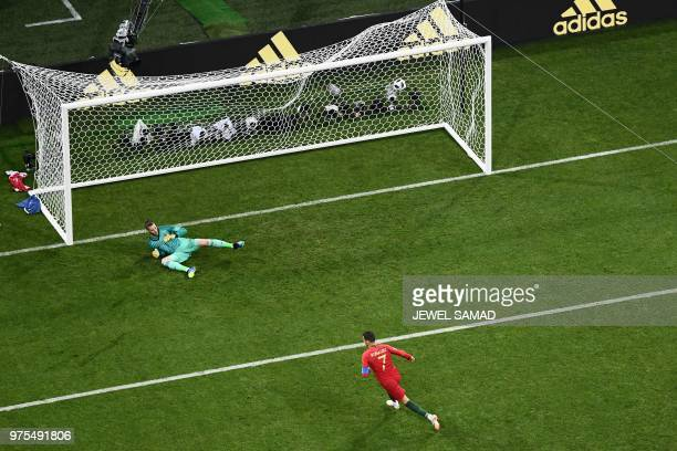 TOPSHOT Portugal's forward Cristiano Ronaldo scores a penalty despite Spain's goalkeeper David De Gea during the Russia 2018 World Cup Group B...