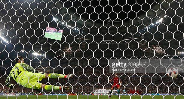 Portugal's forward Cristiano Ronaldo scores the first in a penalty shoot-out during the Euro 2016 quarter-final football match between Poland and...