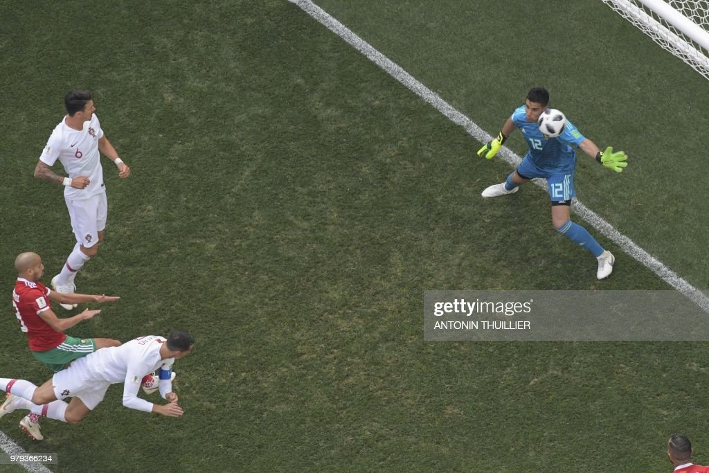 TOPSHOT - Portugal's forward Cristiano Ronaldo (bottom) scores the opening goal during the Russia 2018 World Cup Group B football match between Portugal and Morocco at the Luzhniki Stadium in Moscow on June 20, 2018. (Photo by Antonin THUILLIER / AFP) / RESTRICTED