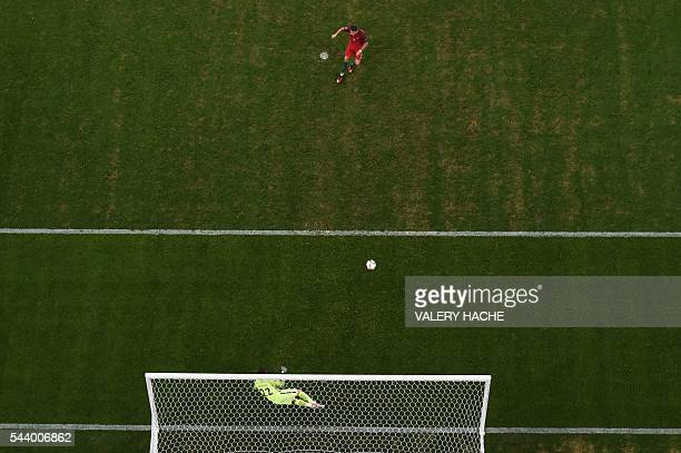 Portugal's forward Cristiano Ronaldo shoots and scores the first in a penalty shootout during the Euro 2016 quarterfinal football match between...